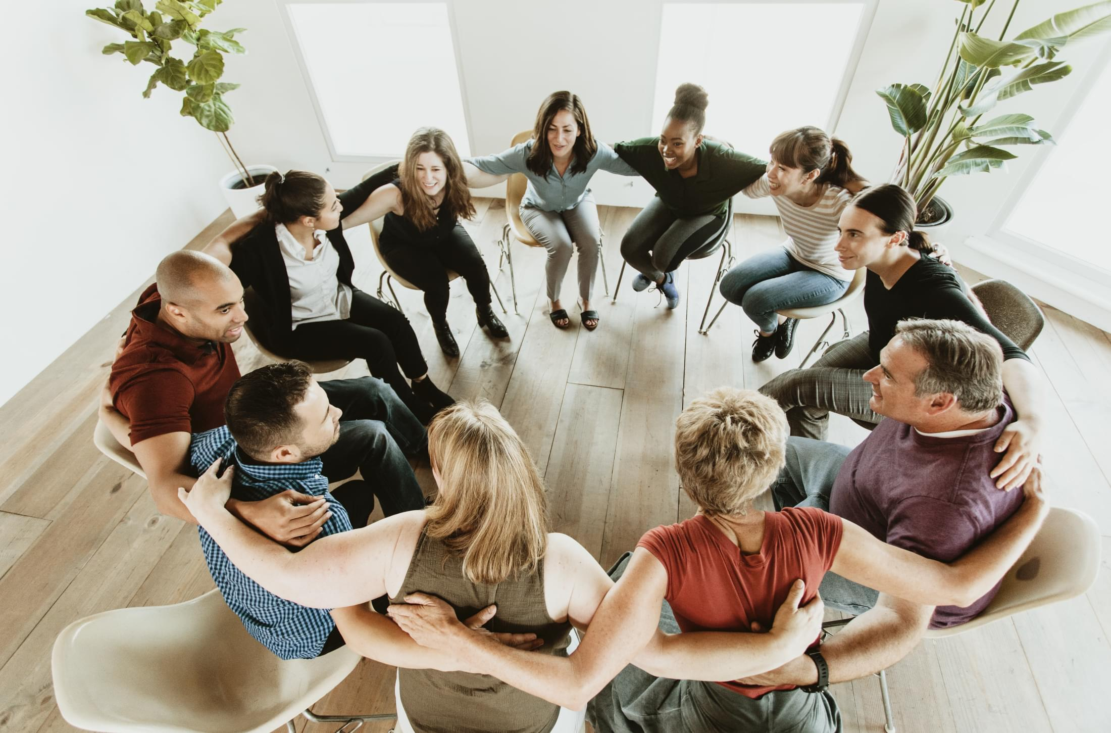 people sitting in a circle with arms around each other